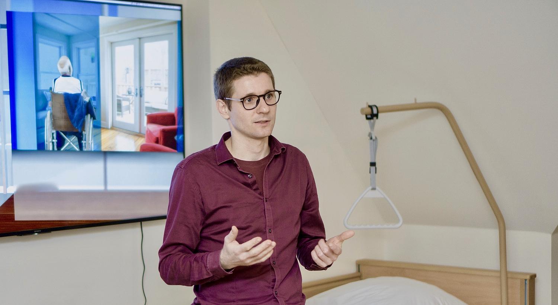 Ein Herr steht im AAL-Labor vor einem Bildschirm und erläutert Dinge.