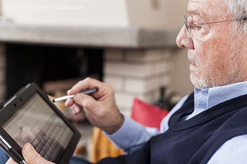 Älterer Mann nutzt einen Eingabestift auf einem Tablett.